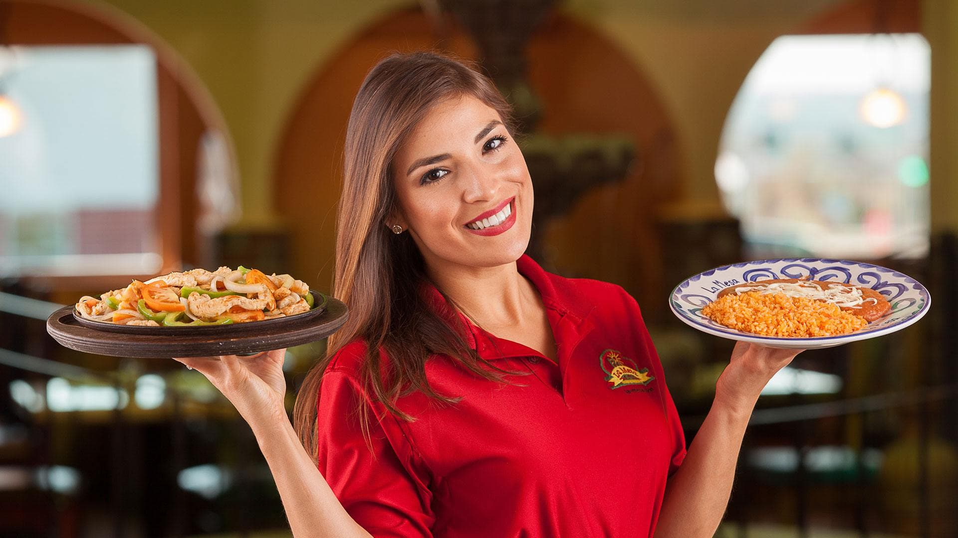 Waitress holding entrees at La Mesa Mexican Restaurant